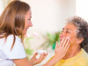 Home health aide applying makeup to a patient.