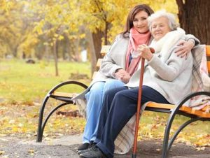 Young caregiver sitting with arm around senior patient on park bench.